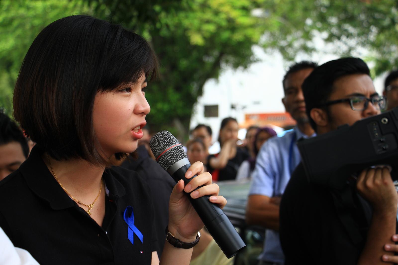 Law student representative Fiona Lim giving a speech, she wears a blue ribbon in solidarity with the students' campaign for freedom of expression