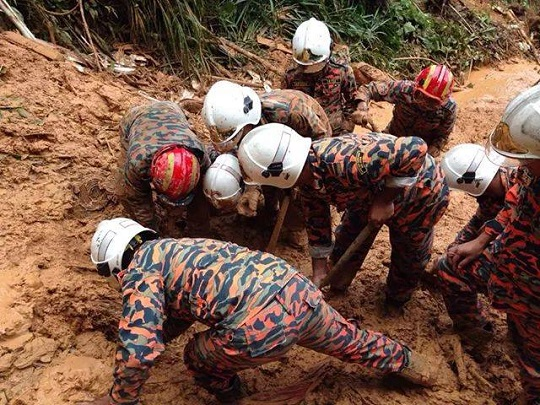 The rescue team ploughing through the mud in the search for two missing people believed to be buried under it. – Pic courtesy of the Malaysian Fire and Rescue Department