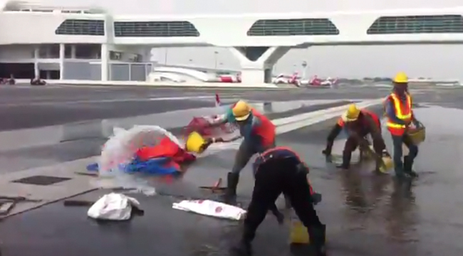 A picture which went viral on social media of workers scooping water off the tarmac at KLIA2